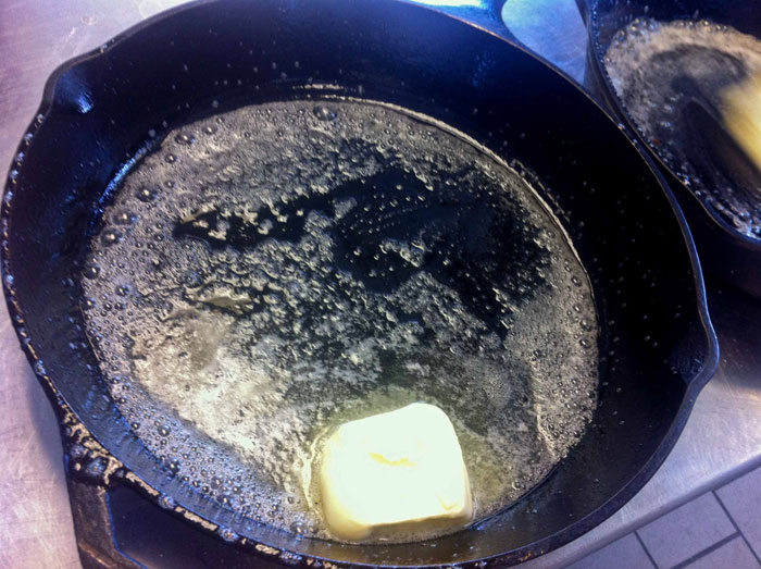 Melt butter in the hot cast iron pan